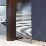 Un vinilo especial con líneas que dan un efecto degradé a la mampara del baño